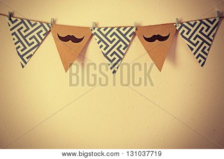 Triangle garland with mustache and pattern on wall