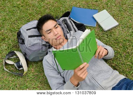 college student lying on a grass with book, laptop,bagat campus