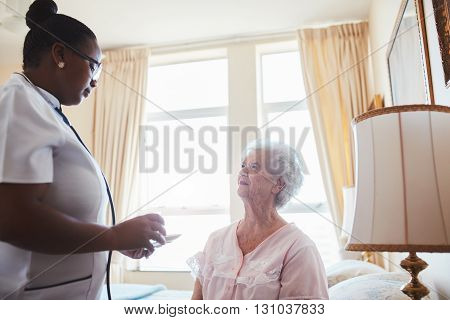 Female care worker nurse assists an elderly female patient with medicines for the day. Home caregiver giving medication dosage to senior woman sitting on bed at home.
