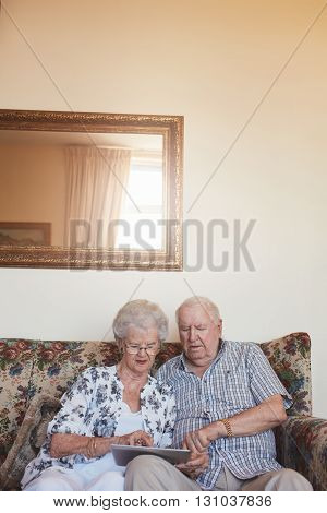Retired Couple At Home Using Digital Tablet