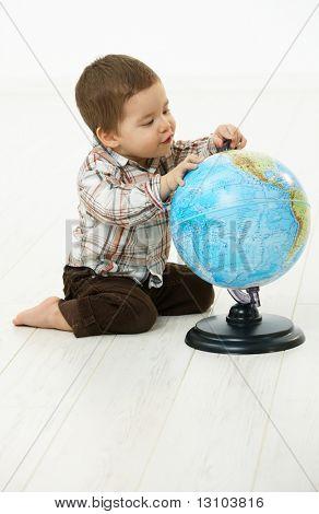 Niedlichen kleinen Kind (2-3 Jahre) sitting on Floor spielen mit Globus over white Background.