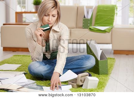 Worried woman checking documents, holding credit card, sitting on floor with crossed legs at home.