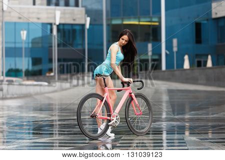 Sexy girl on bicycle. Young slim sexy sportive woman in blue shorts and white snickers long-haired, sensual posing on pink fix bicycle at grey background in urban city enviroment. Soft toned.