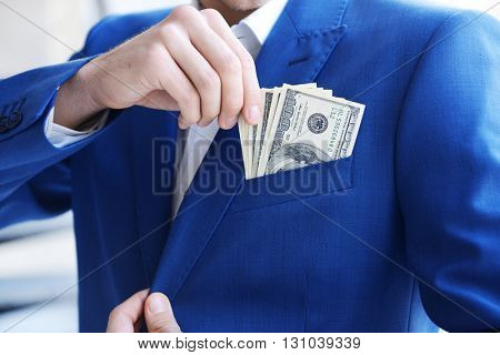 Man getting dollar banknotes out of suit pocket