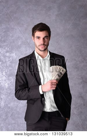 Attractive man in a suit holding fan of dollar banknotes on grey background