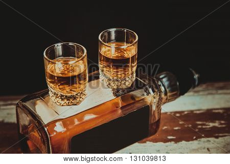 Two Glasses Of Whiskey Are On The Bottle With Alcohol