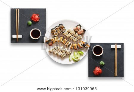 Japanese food restaurant, sushi unagi gunkan roll plate or platter set. Set for two with chopsticks, ginger, soy sauce and wasabi. Sushi at black stone isolated at white background. Top view, Flat lay