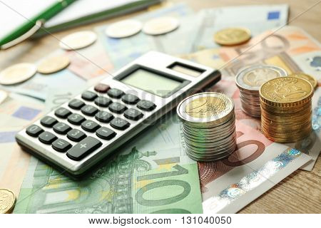 Money concept. Grey calculator with coins and notebook, close up
