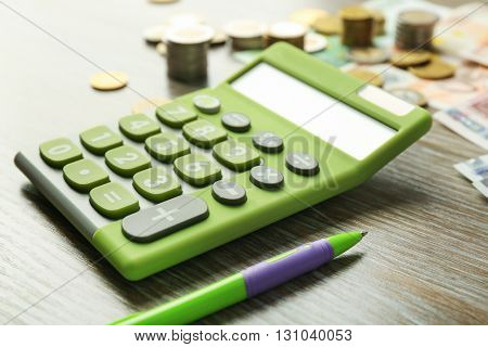 Money concept. Green calculator with banknotes and coins on wooden table
