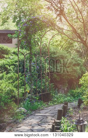 Beautiful landscape design, garden path with park light, wooden fence and metal arch, evergreen bushes and shrubs in sunlight. Modern landscaping. Summer garden or park design.