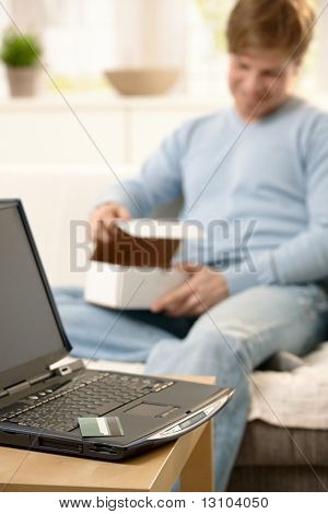 Laptop computer and credit card in focus, guy in background opening box purchased online.