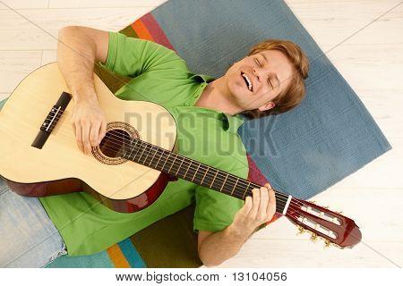 Glücklich Jüngling auf Boden mit Gitarre, lächelnd in high Angle View.
