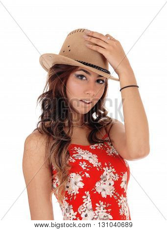 A pretty young woman in a red dress and curly brown hair putting on a cowboy hat isolated for white background.