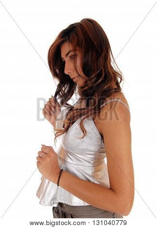 A lovely young woman standing in profile with long brunette hair in deep thoughts isolated for white background.