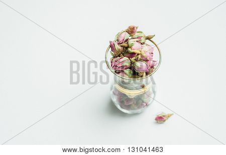 Tiny dried rose buds in a typical arabic tea glass. Middle eastern food and ingredients.