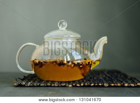 Chinese herbal tea brewing in a a transparent glass tea pot.