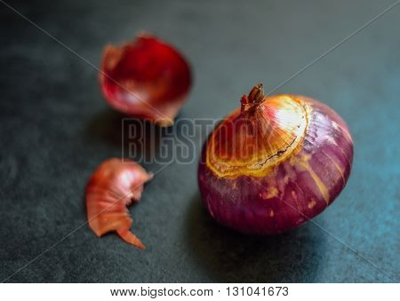 An organic purple color onion on dark background with few pieces of peel.