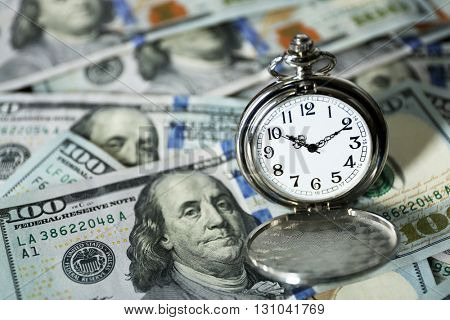Time is money concept with pocket watch and dollars bills closeup