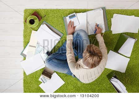 Woman sitting on living room floor, surrounded with bills and documents, using calculator, drinking coffee, in overhead view.