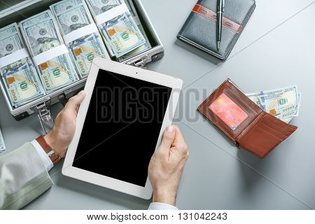 Businessman with tablet and case full of money