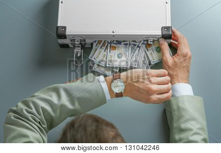 Businessman with case full of money on grey background