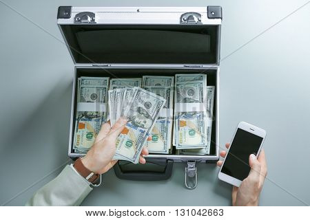 Businessman with money and cellphone on grey background