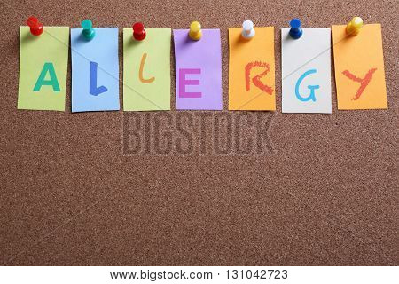 Word ALLERGY pinned on cork board