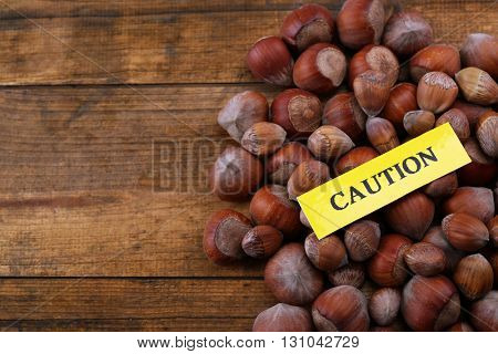 Allergy food concept. Pile of hazelnuts on wooden background