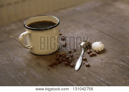 Mug of coffee with zephyr on wooden table
