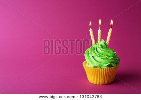 Birthday cupcake with candles on pink background