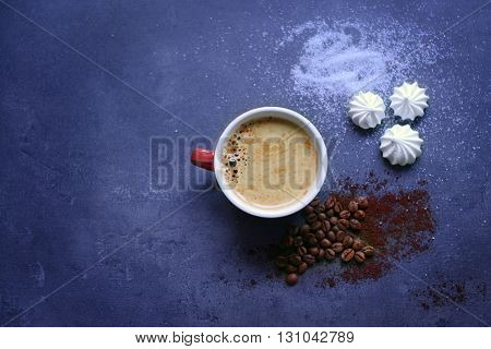 Cup of coffee with zephyr on dark blue table