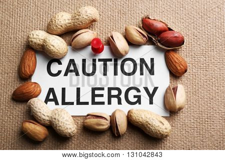 Sign CAUTION ALLERGY with nuts on textured background