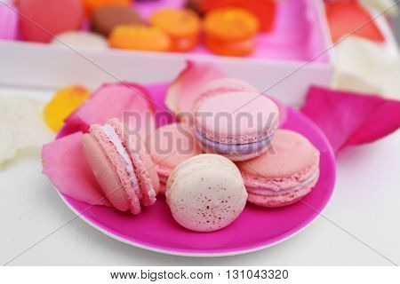 Fresh macaroons on pink plate, closeup