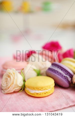 Fresh macaroons and roses on the table indoors