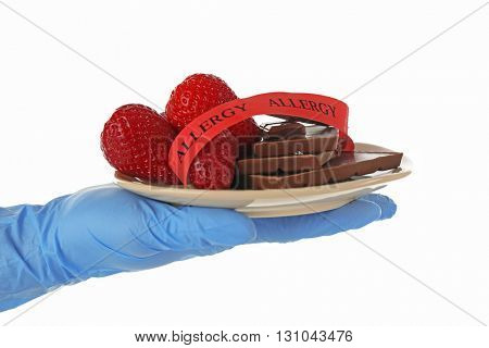 Allergic food concept. Hand in glove holding chocolate and strawberry isolated on white