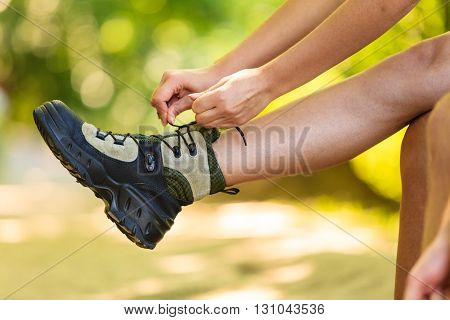 Outdoor leisure holidays trip survival trekking concept. Hiker preparing their footwear. Female tourist checking her boots before further travel.