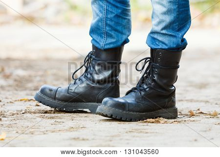 Nature outdoor foliage relax concept. Man in black boots. Male in leather footwear jeans trousers standing outside.
