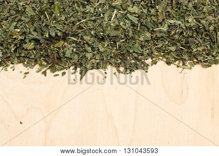 Healthy food healing herbs alternative herbal medicine concept. Border frame of dried herb nettle leaves on wooden board with copy space
