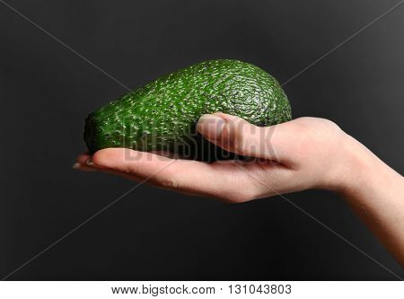 Female hand holding avocado on dark background