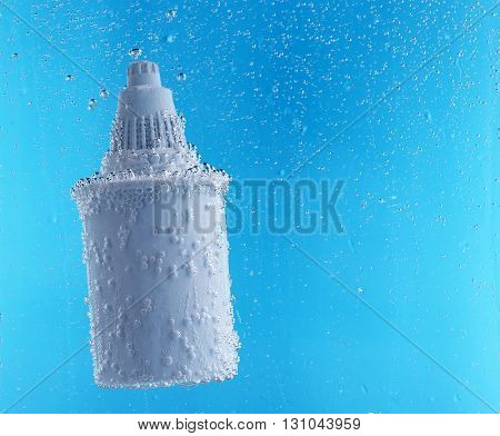 Filter cartridge deep in the water, on blue background