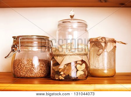 real comfort wooden kitchen with breakfast ingredients close up in glass, honey, oatmeal, milk, muesli, healthy food concept