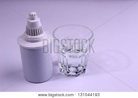 Filter cartridge and a glass of water, isolated on white