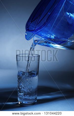 Filter jug pouring water in the glass, on dark background, close-up