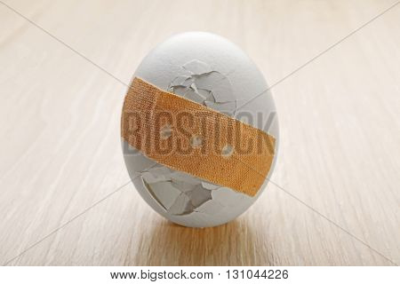 Cracked egg wrapped in court plaster on wooden background