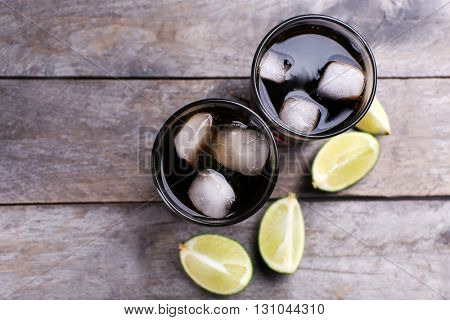 Glasses of soda water and sliced lime on wooden table, top view