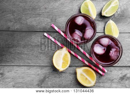 Glasses of red soda water and sliced lemon on wooden table, top view