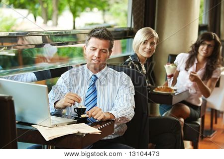 Businessman using laptop in cafe, young women in the background recognized him. Selective focus on businessman.