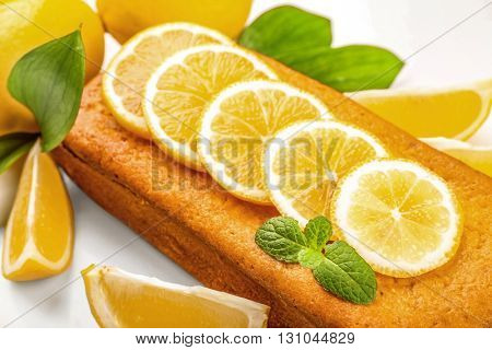Delicious citrus cake loaf with lemons on white background