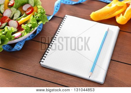 Vegetable salad and blank notebook on wooden table closeup