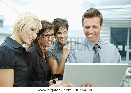 Team of business people looking at laptop computer outdoor in front of office building.